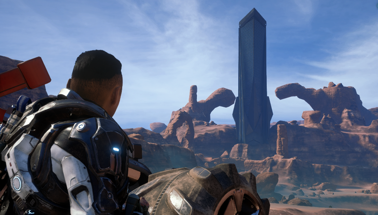 The customizable protagonist, a human named Ryder, stands next to the tire of his vehicle while looking off in the distance at a large towering structure called a Monolith.